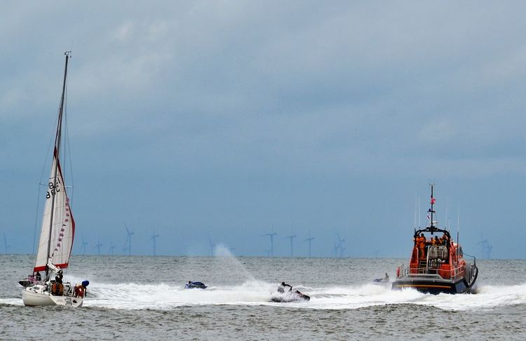 Jet skis captured between a sailing school yacht and an RNLI Lifeboat vessel on Morecambe Bay between Fleetwood and Knott End on Sea, Lancashire UK. Boat Day Horizon Over Water Jet Ski Lifeboat Motion Nautical Vessel Outdoors RNLI Sailing Boat Scenics Sea Sea And Sky Seascape Seaspray Sky The Great Outdoors - 2017 EyeEm Awards Wave Wind Farm Yacht
