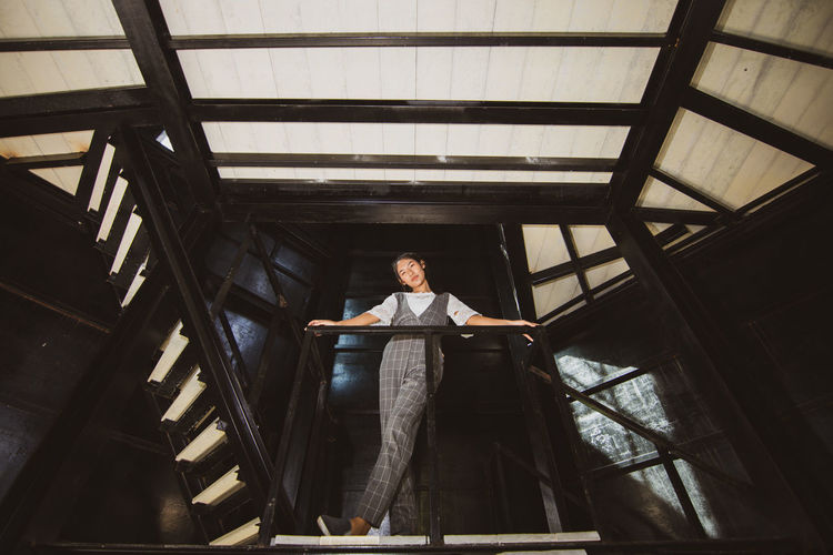 Low Angle View Of Young Woman Standing On Staircase