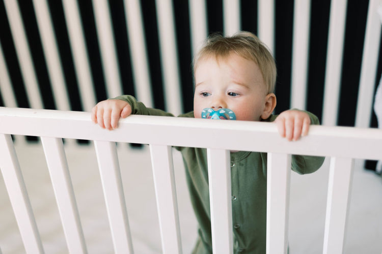 Portrait of boy looking away while standing on railing