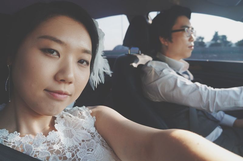 Portrait of mid adult woman with man sitting in car