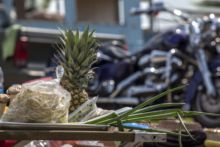 Various fruits and vegetables on table against motorcycle