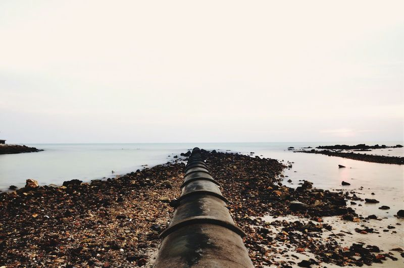 Scenic view of sea against sky with pipeline as a leading line