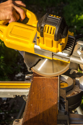 Circular Saw Close-up Construction Industry Danger Day Equipment Hand Human Body Part Human Hand Industry Machinery Metal Occupation One Person Power Tool Real People Saw Wood - Material Work Tool Working Yellow