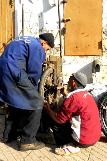 Atelier Cyclist Day Full Length Mecanicien Men Occupation Outdoors Real People Reparation Roue  Teamwork Working