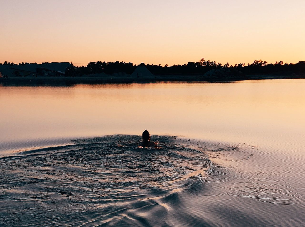 Person swimming in lake during sunset