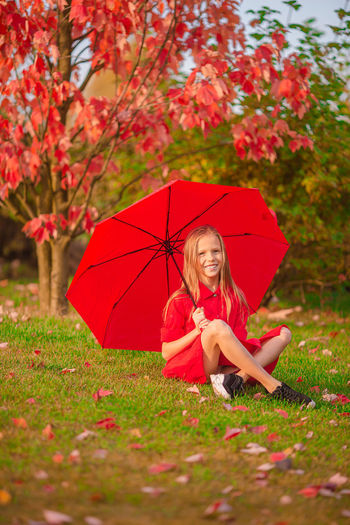 Full length of a girl with red umbrella