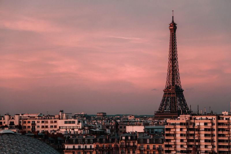 Eiffel tower amidst buildings against sky during sunset