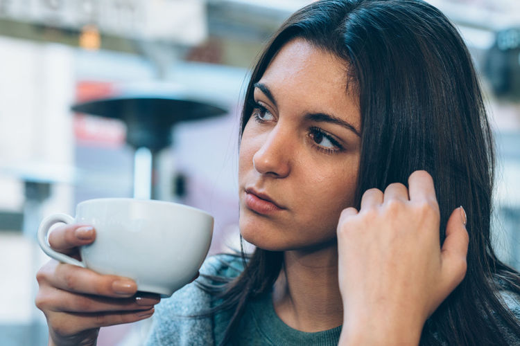 Close-up of thoughtful woman having coffee at sidewalk cafe