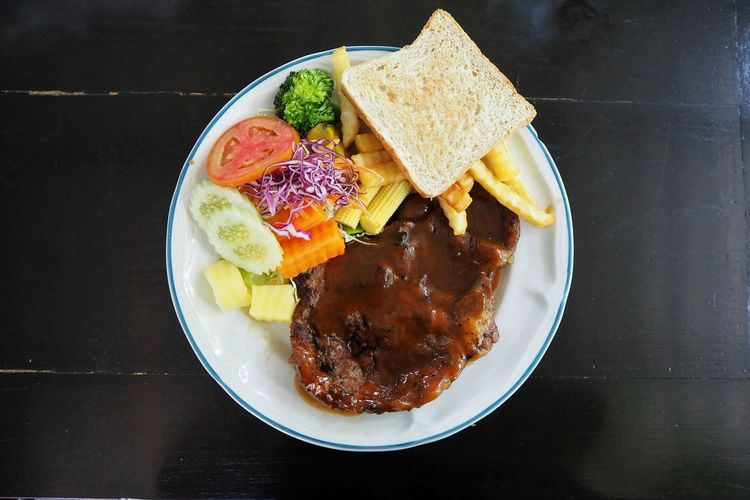 Top view of pork steak served witg salad and frenchfire put on the table Steak Salad Vegetable Toast French Fries Pork Porkshop Restuarant Dinner Lunch Yummy Delicious Tasty Taste Fruit Plate Bowl High Angle View Black Background Close-up Food And Drink Served Meat Beef Sauce