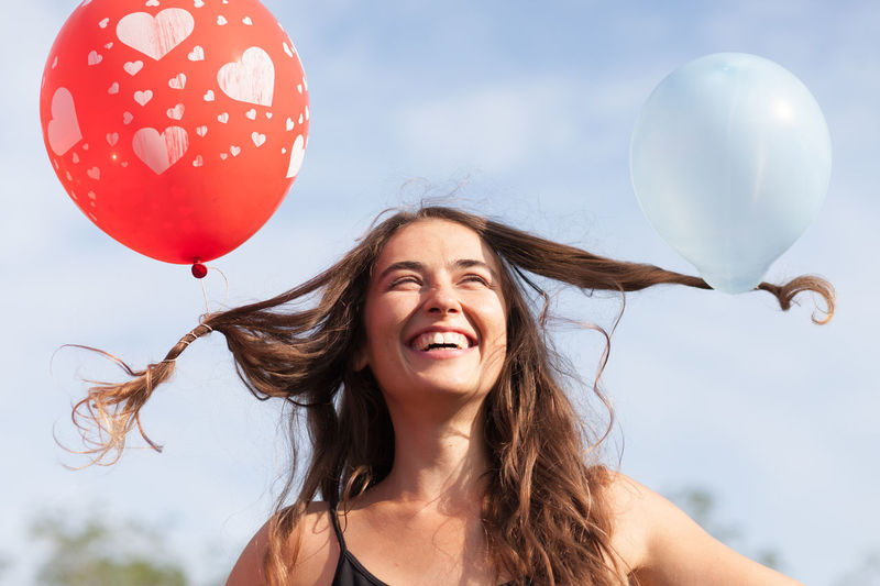 young woman with balloons in her hair Adult Attractive Balloon Beautiful Woman Brunette Carefree Cheerful Emotion Enjoyment Freedom Fun Happiness Headshot Joy Long Hair Lovely One Person Outdoors Portrait Positive Emotion Sky Smiling Wind Women Young Adult