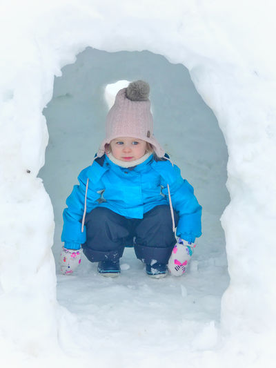 Child Childhood Clothing Cold Temperature Day Extreme Weather Front View Full Length Hat Igloo Innocence Knit Hat Leisure Activity Lifestyles Nature One Person Outdoors Playing Real People Snow Warm Clothing White Color Winter