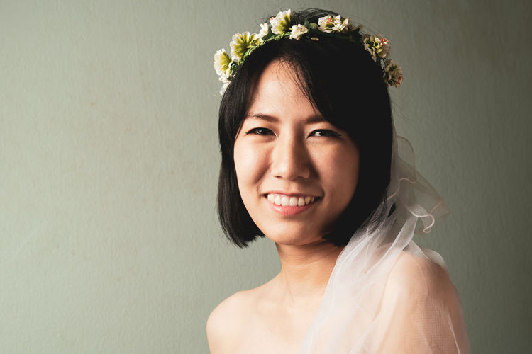 Portrait of smiling bride against wall