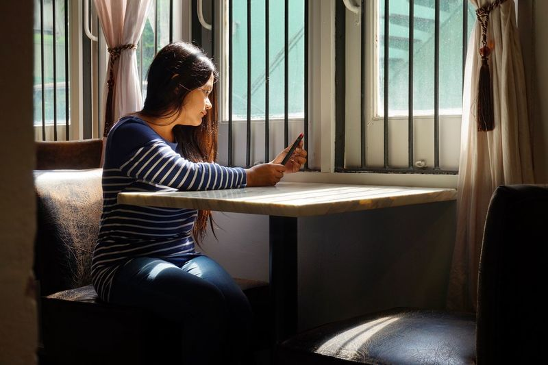 Young Woman Using Mobile Phone At Table