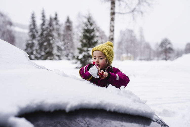 Portrait of girl in snow covered park during winter