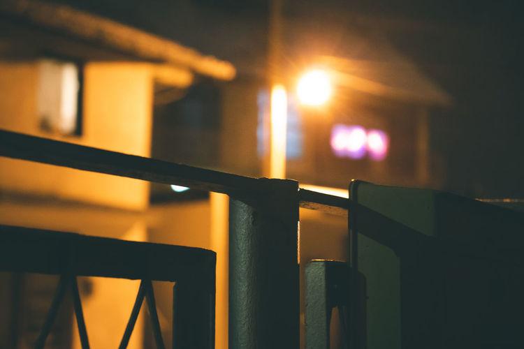 Close-up of illuminated railing against sky during sunset