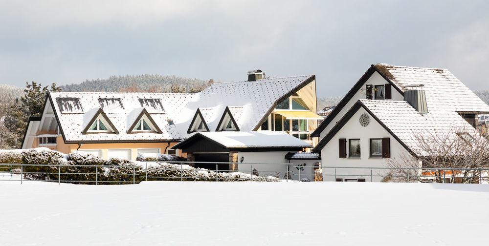 Houses on snow covered house against sky