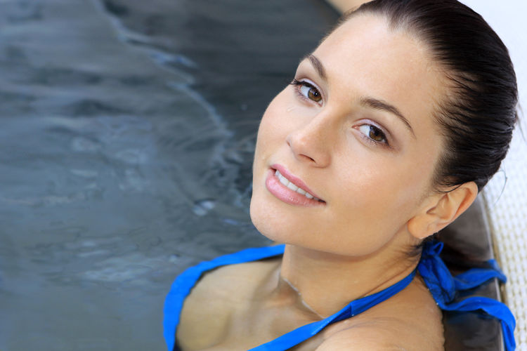 Close-up portrait of young woman in swimming pool at spa
