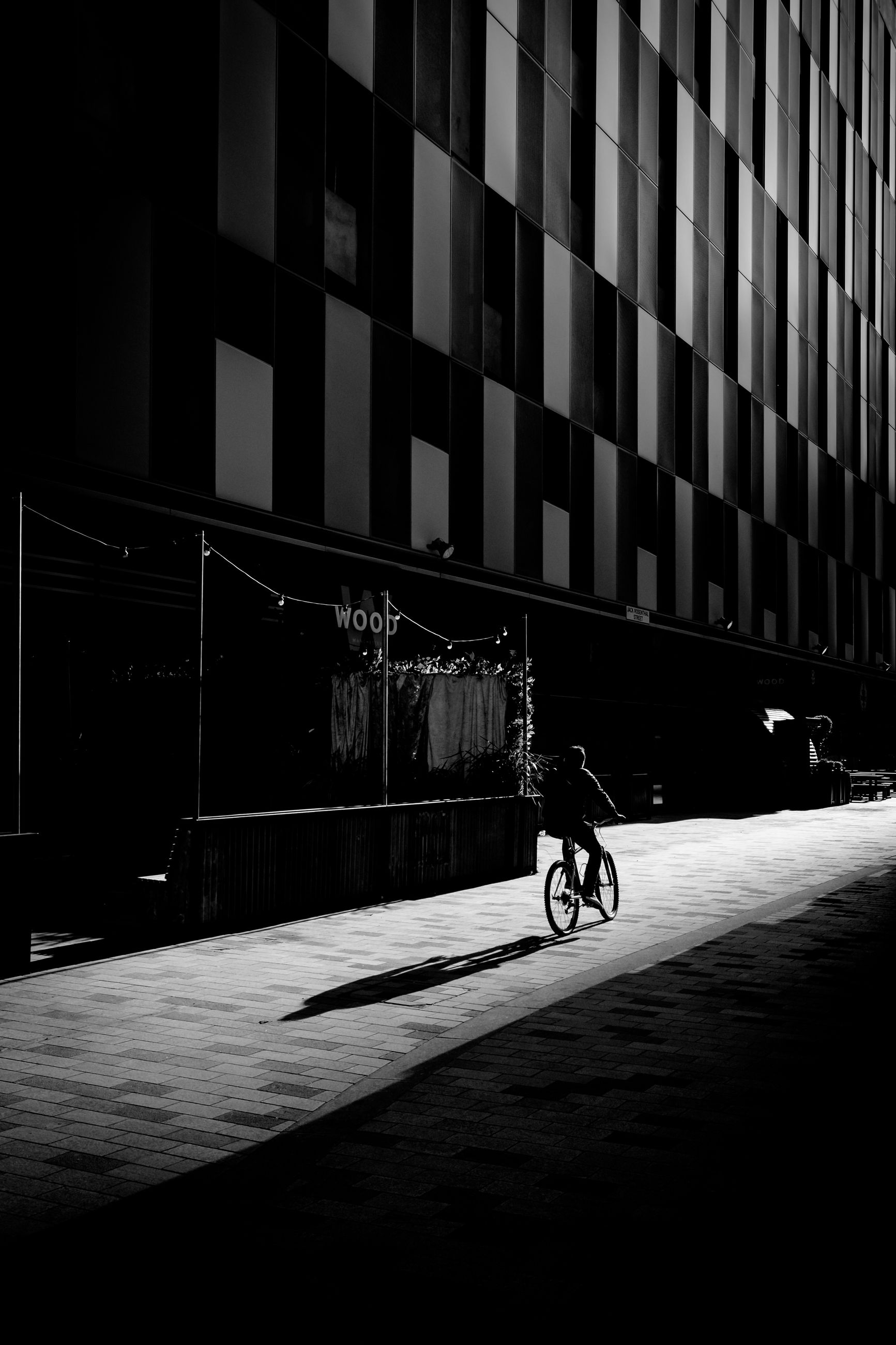 architecture, transportation, built structure, building exterior, bicycle, city, land vehicle, mode of transportation, one person, ride, riding, real people, building, men, sport, cycling, street, lifestyles, motion, outdoors, dark, office building exterior