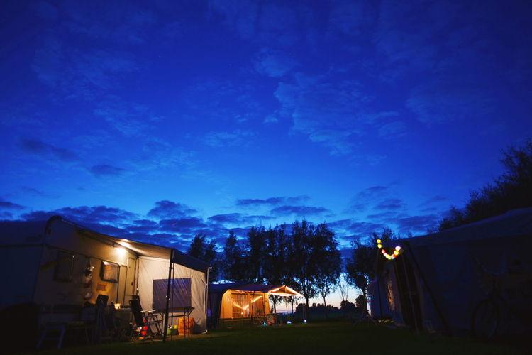 Illuminated houses against blue sky at night