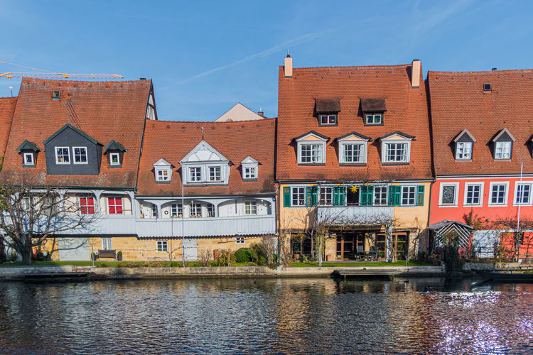 Houses by canal against sky in city