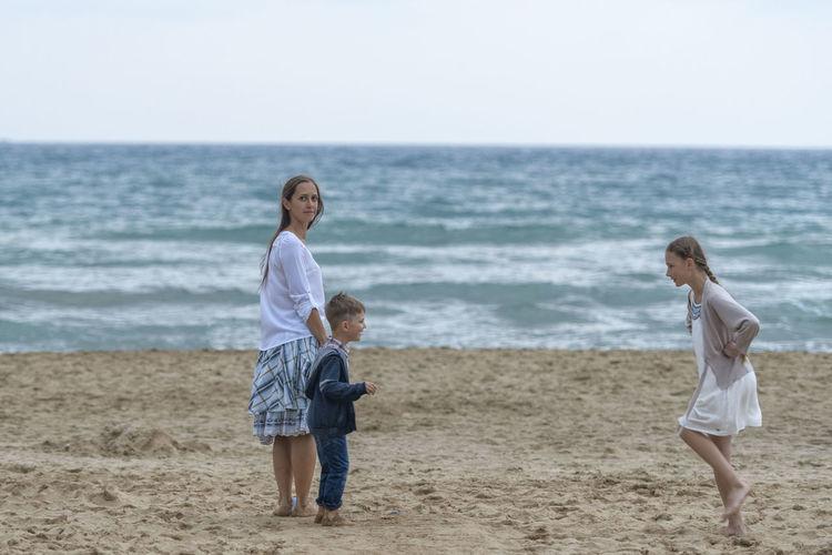 Full length of family at beach against sky