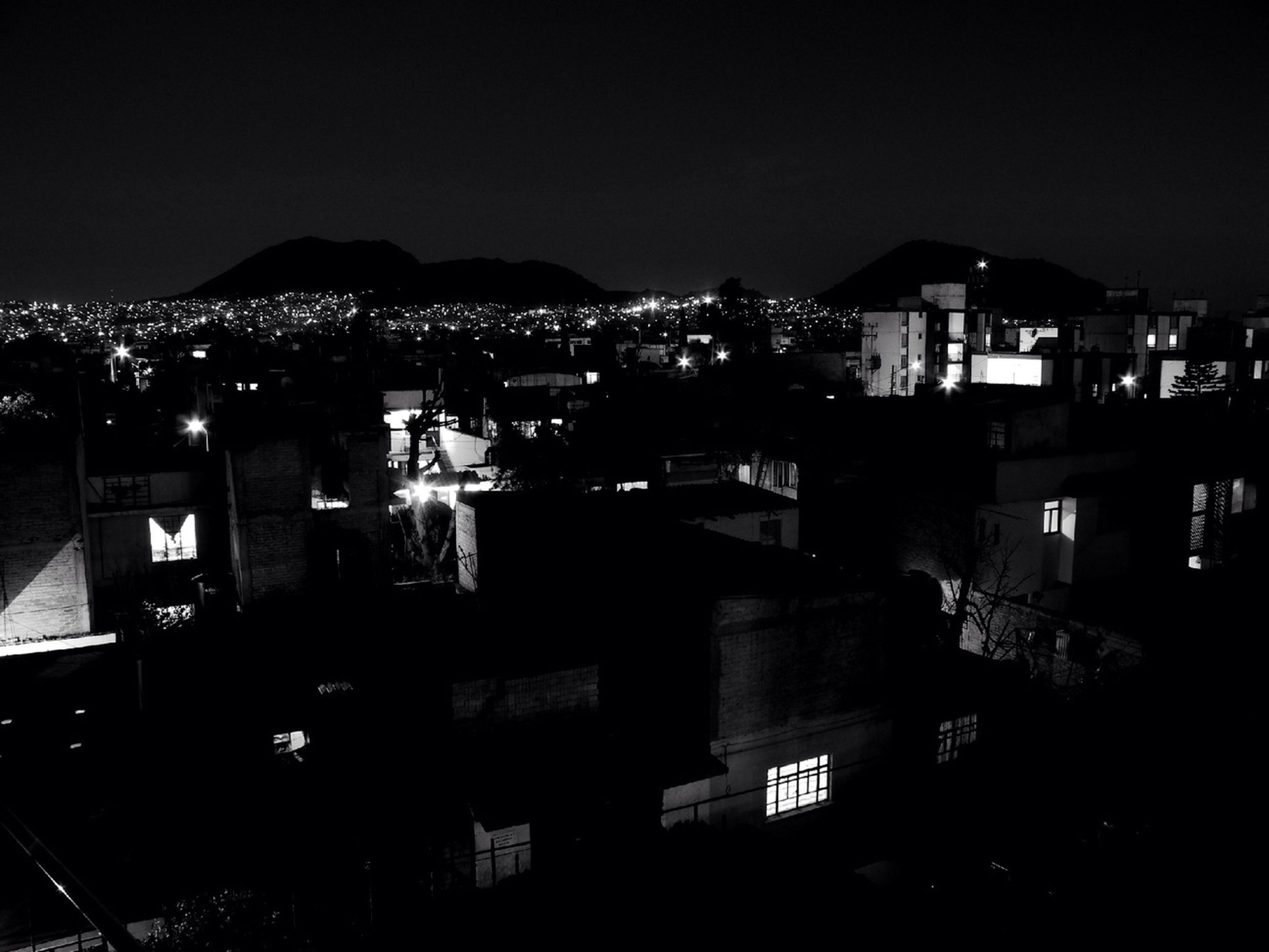 building exterior, illuminated, night, architecture, built structure, city, cityscape, residential building, residential structure, residential district, house, high angle view, copy space, clear sky, crowded, mountain, town, dark, outdoors, dusk