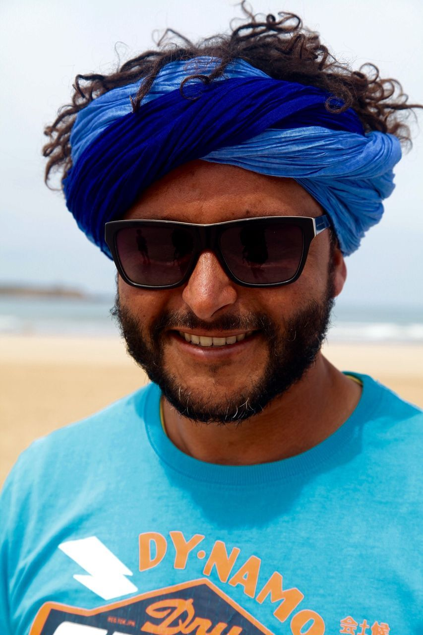 sunglasses, front view, one person, young adult, happiness, real people, portrait, young men, smiling, looking at camera, casual clothing, headshot, mid adult, leisure activity, day, lifestyles, focus on foreground, t-shirt, beard, outdoors, beach, close-up, nature, adult, adults only, people