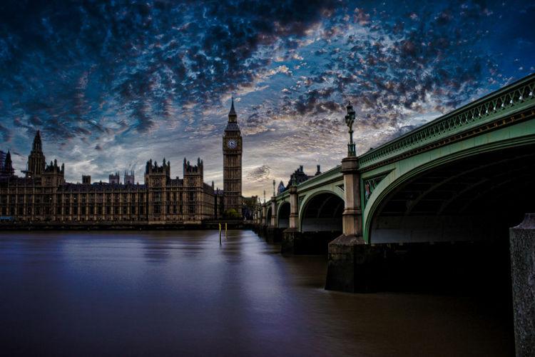 Westminster bridge over river in city at dusk