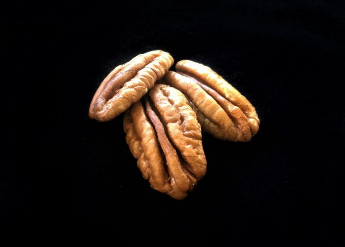 Pecans on the half shell. Black Background Studio Shot Pecan Pecans Still Life Food Healthy Eating Close-up Tree Nuts Tree Crop Nuts Pecan Halves Black Background Ready-to-eat Horizontal