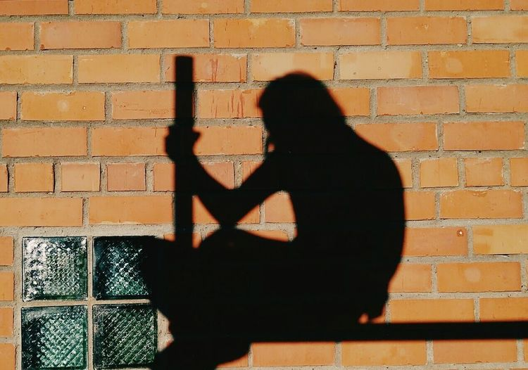 Shadow of woman standing on brick wall
