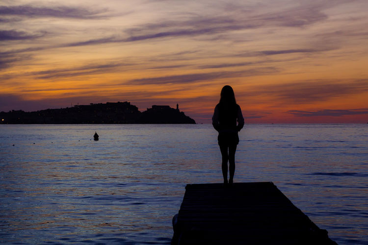Silhouette Woman Standing On Pier Against Sky During Sunset