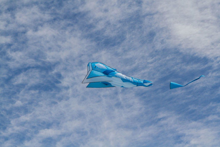 Low angle view of giant kite flying against blue sky