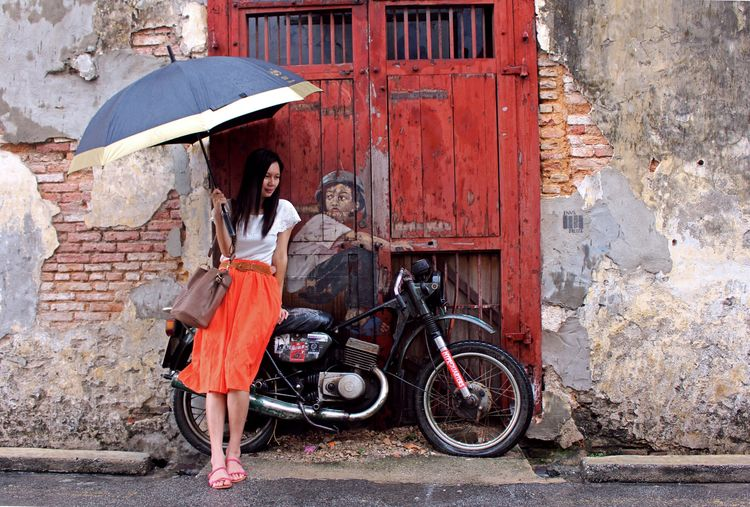 An Asian Woman in Orange Skirt holding an Umbrella, Stands beside a Street Art Mural 'boy and bike', illustrated by Lithuanian artist Ernest Zacharevic in Georgetown, Penang, Malaysia Feel The Journey Original Experiences