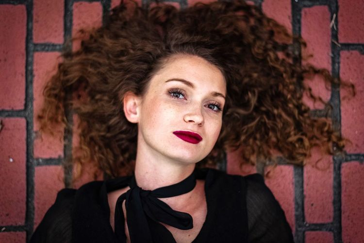 Portrait Headshot Curly Hair Hairstyle Hair Beauty Young Adult Front View Beautiful Woman One Person Women Young Women Lifestyles Real People Looking At Camera Lipstick Adult Make-up Contemplation Brick
