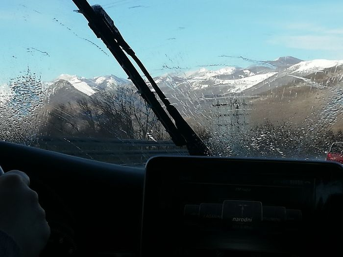View of cars on snowcapped mountains seen through car windshield