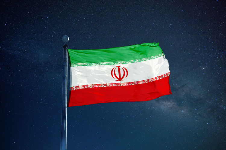 Low angle view of iranian flag against star field sky