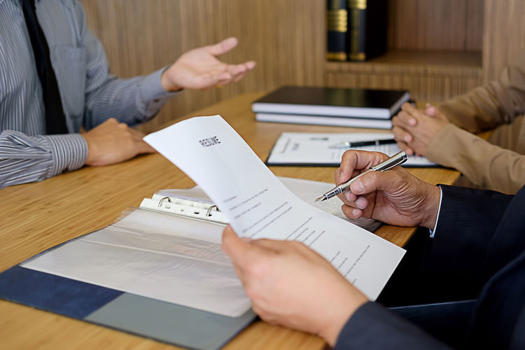 Midsection of business people interviewing candidate on desk