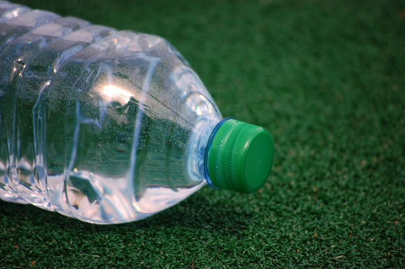 Plastic Bottle Close-up Day Environmental Conservation Environmental Issues Fuel And Power Generation Garden Hose Glass - Material Grass Green Color Illuminated Lawn Light Bulb Lighting Equipment Nature No People Outdoors Plant Plastic Single Object Sport Transparent Water Water Bottle