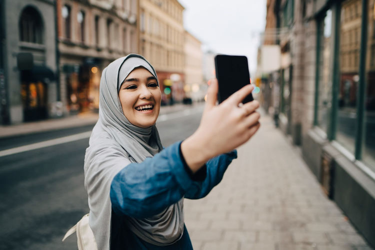 Portrait of smiling young woman using mobile phone in city