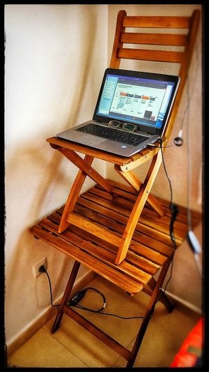 """Improvised """"standing desk"""" found in wardrobe of house rental. Sometimes you just have to think💭 """"outside of the box"""" 📦 Windows 10 Laptop Standing Desk Garden Furniture Chair Indoors  Table Technology No People Close-up Modern Workplace Culture"""