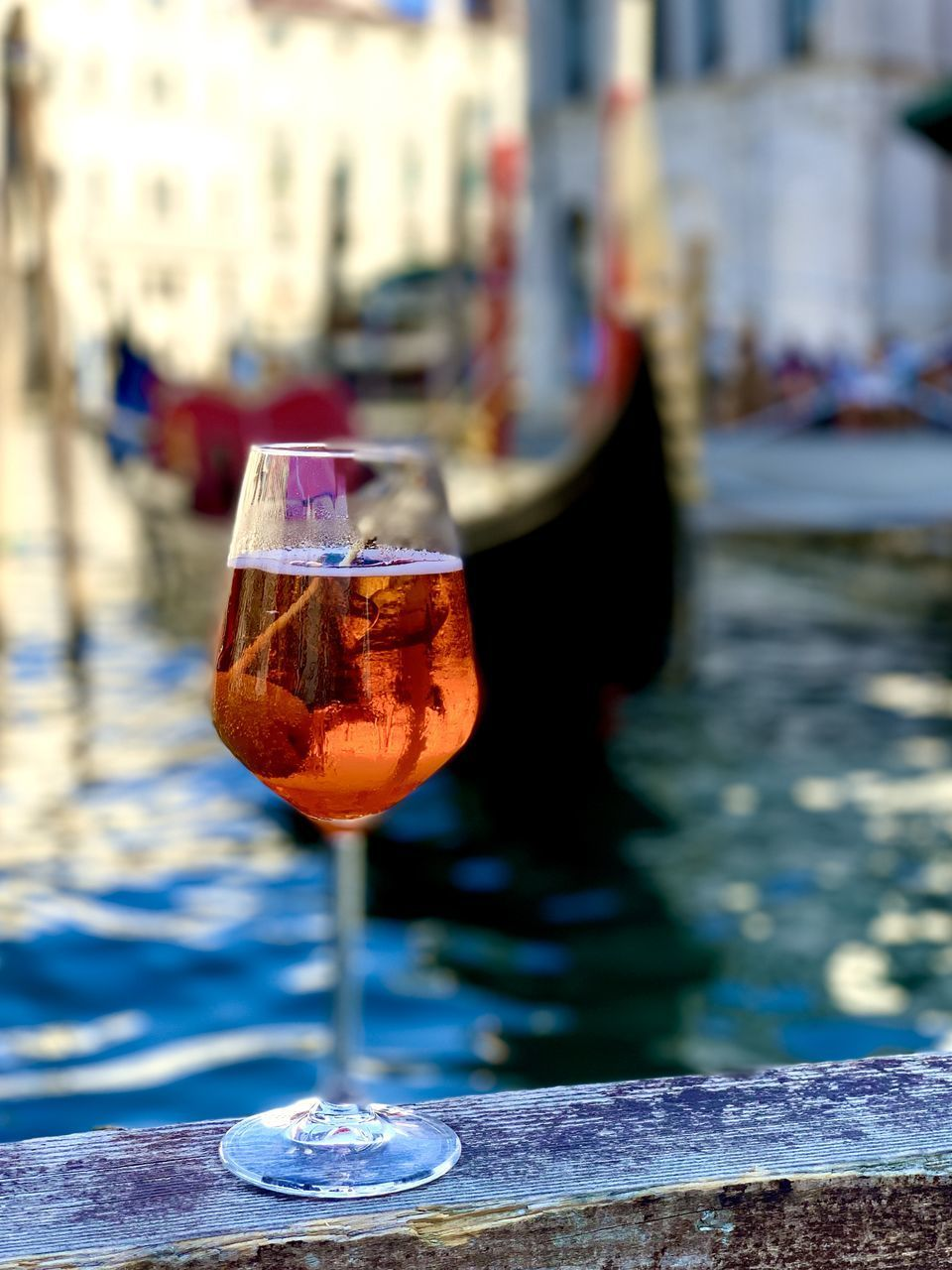 CLOSE-UP OF WINE GLASS ON TABLE AGAINST CANAL