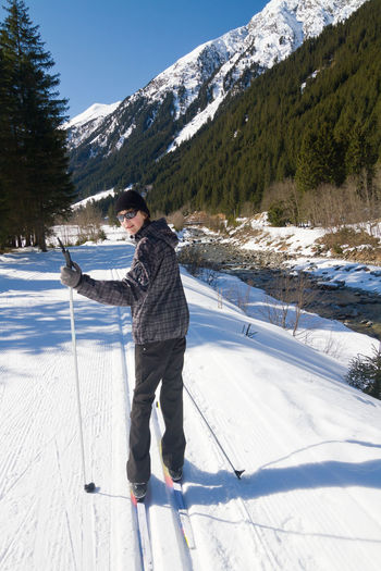 Full length portrait of teenage boy enjoying cross-country skiing in alps