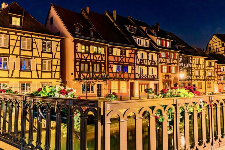 Colmar canal amidst buildings at night