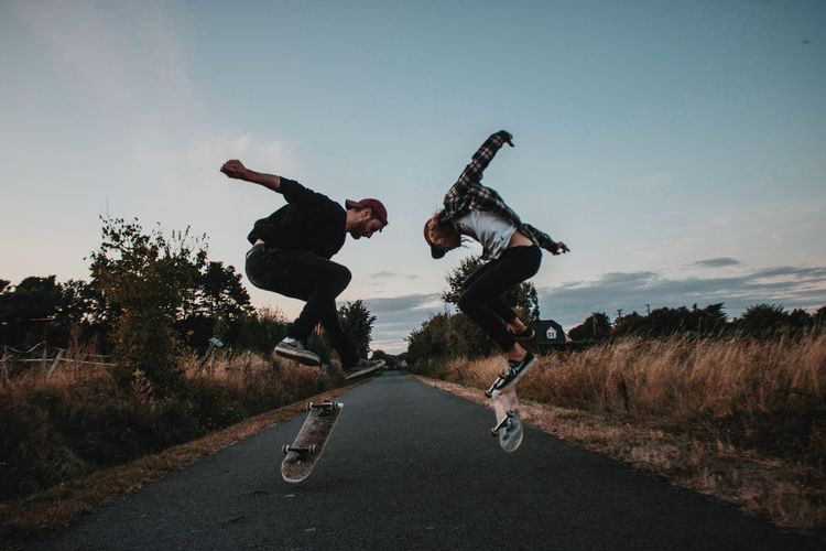 Sky Full Length Plant Real People Road Tree Leisure Activity Jumping Mid-air Nature Casual Clothing Lifestyles Motion People Enjoyment Day Skate Skateboarding Outdoors Skill  Men Transportation Vitality Human Arm Friendship