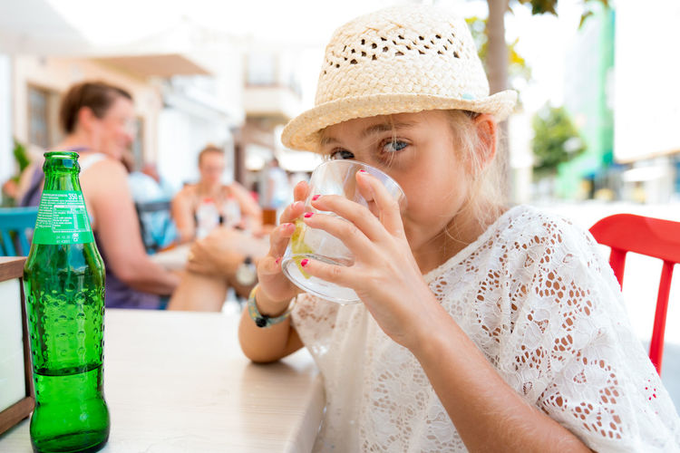 Portrait of girl drinking juice at outdoor cafe