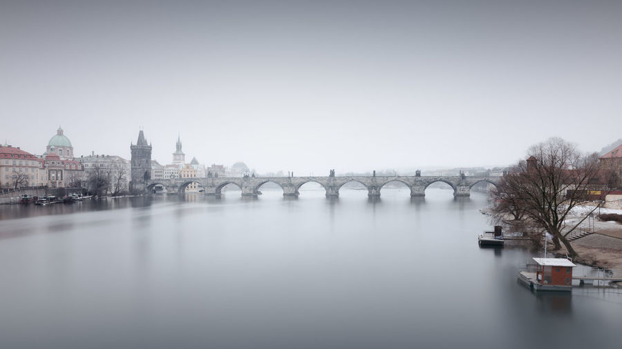 Charles bridge over vltava river against sky in city during foggy weather