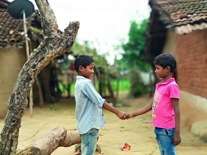Side View Of Male Friends Shaking Hands While Standing In Village