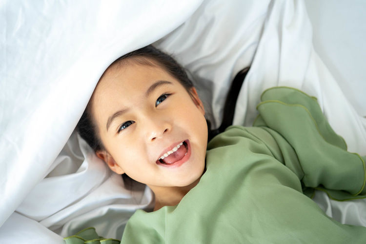 Portrait of baby girl lying on bed