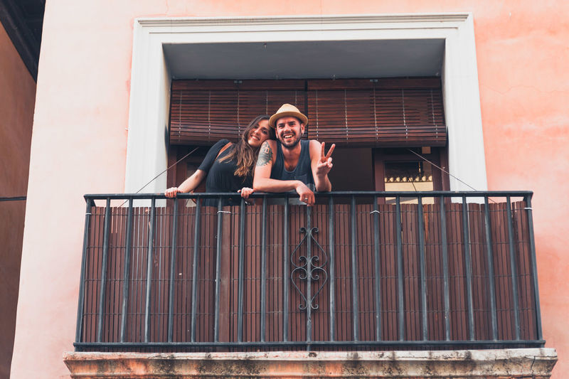Portrait of smiling young man showing peace sign by girlfriend at balcony