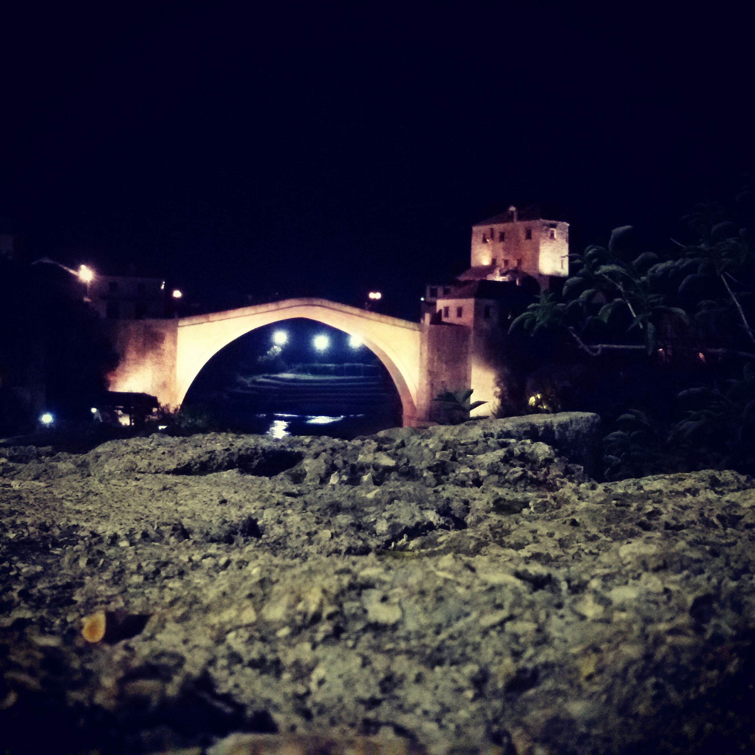 night, transportation, illuminated, copy space, clear sky, built structure, land vehicle, architecture, mode of transport, bridge - man made structure, connection, car, surface level, rock - object, water, outdoors, river, motion, building exterior, road